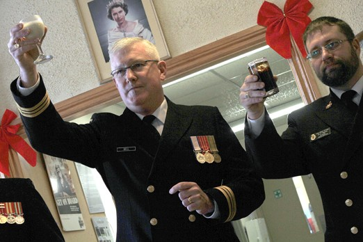 Lt.-Cmdr John Bell, commander of HMCS Griffon (left) and Petty Officer First Class Dale Warren toast the Queen at one of two New Year