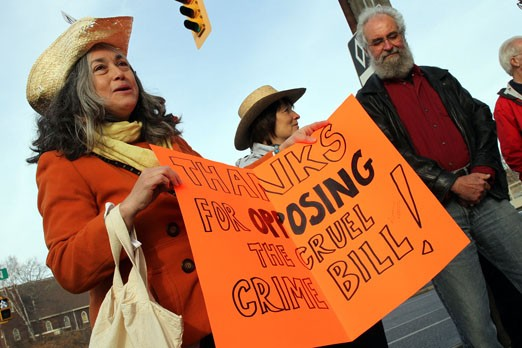 Protestor Robin Faye (left) joined about a dozen others Thursday outside the offices of NDP MP Bruce Hyer, opposing the Conservative government
