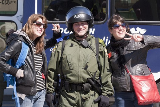 Two female demonstrators pose with a police officer in riot gear after a tentative agreement with students became public Saturday, May 5, 2012 as the Quebec Liberal Party is meeting in Victoriaville, Que..