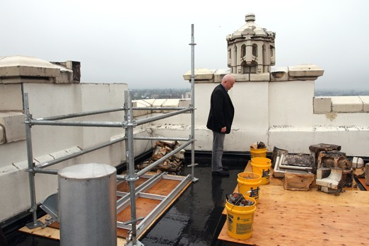 Michael Smith stands on top of the Whalen Building Thursday afternoon. The damaged turret, which was to the left of the photo, has been removed.