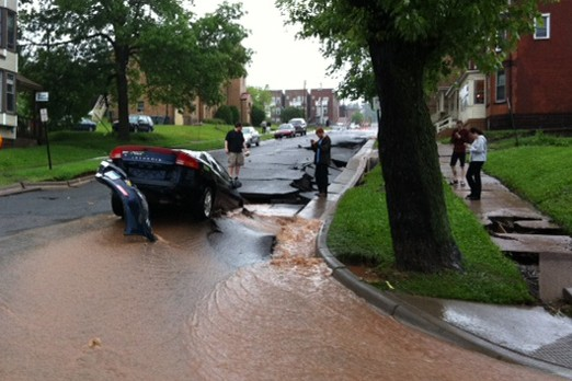 A car rests in a sinkhole on Wednesday after floodwaters and heavy rains ravaged Duluth.