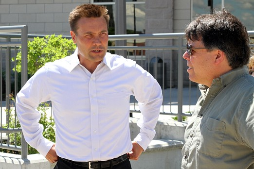 Tornado Medical Systems CEO Stefan Larson (left) speaks with Coun. Mark Bentz on Friday outside city hall, a day after announcing he was laying off six of seven employees at his company
