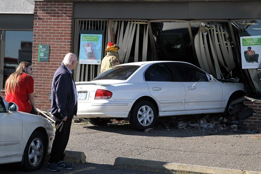 Witnesses stand nearby Monday after an elderly woman crashed her Hyundai Sonata through the front window of TD Canada Trust