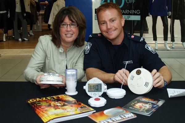 Nancy Patterson, Canadian Hearing Society and Thunder Bay Fire Rescue Public Education Officer Anthony Stokaluk display visual smoke alarms at the Time to Change Your Batteries smoke alarm awareness event at Intercity Shopping Centre on Friday.