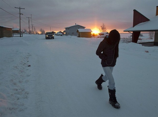 A girl walks along the streets at sunrise December 18, 2012, on the Fort Hope First Nation, Ont.