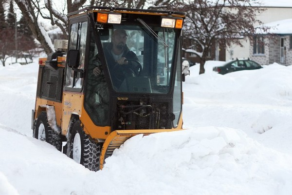 A sidewalk plow works on Ryerson Crescent on Saturday afternoon.