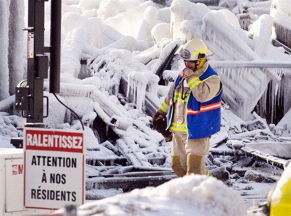 "An emergency worker walks past a sign that reads ""Look out for our residents"" as the search for victims of a seniors residence fire continues Friday, January 24, 2014 in L"