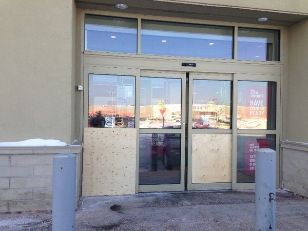 Boarded up windows show the destruction caused by four male suspects who broke into an LCBO early Monday morning. City police are still looking for the four men believed to be responsible for the break-in.