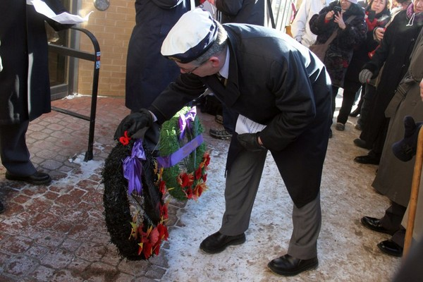 A veteran places a poppy on a wreath laid outside the city