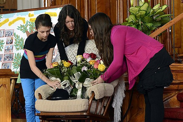 Girls place flowers on a chair at a memorial service Saturday, Feb. 1, 2014 in L