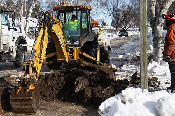 A worker observes as equipment digs to access a broken water main on Isabella Street on Tuesday afternoon