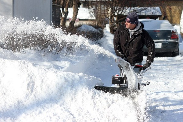 FILE -- A city resident snowblows his driveway last Friday after a heavy snowfall.