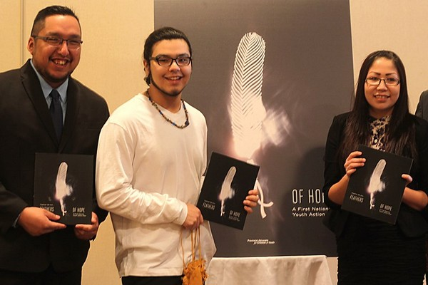 Presenters Cam Meshake (left), Ryan Hunter and Meaghan Masakeyash display copies of the Feathers for Hope: A First Nations Youth Action Plan at the Thunder Bay release of the report at the Best Western Nor