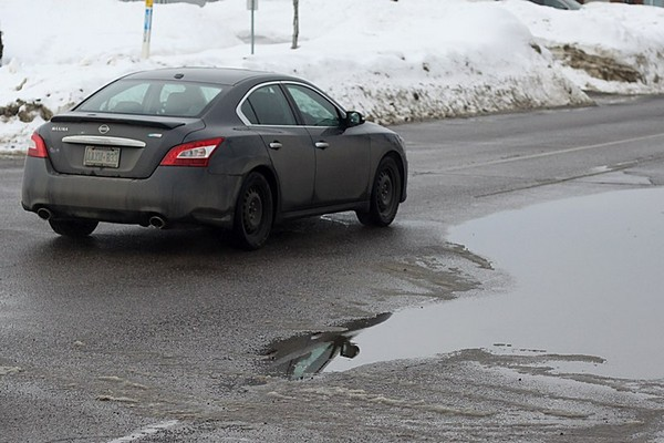 A motorist nearly comes into contact with a substance that was formerly ice and snow, which now forms what people in warmer climates call a puddle.
