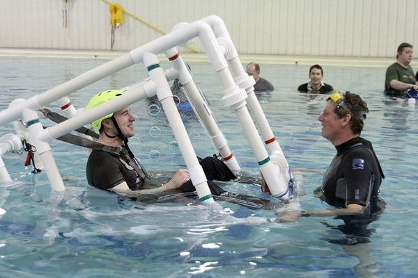 Confederation College student Ryan Kelly (left) is trained Friday at Lakehead University's pool on the basics of escaping a downed aircraft capsized in water.