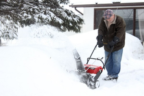 A Jewell Street homeowner clears his driveway Thursday morning.