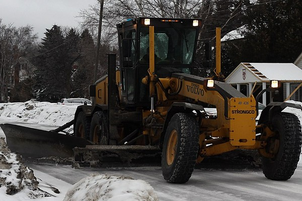 A city snowplow works to clear snow from a residential street on Tuesday morning.