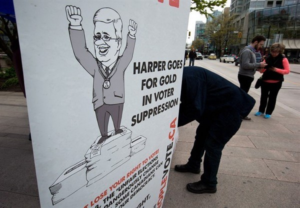 People sign a petition opposing the Fair Elections Act in Vancouver, B.C., on Saturday April 26, 2014.