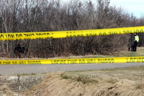 Police investigate a wooded area Monday afternoon.