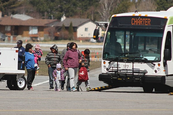 Evacuees from the Kashechewan First Nation prepare to board a bus after arriving in the city on Sunday. Officials expect to host 600 evacuees by the end of the weekend.