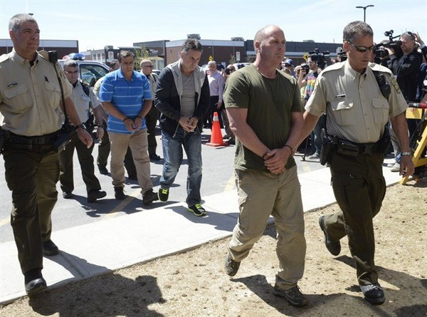 Former Montreal Maine and Atlantic Railway Ltd. employees Thomas Harding, right, Jean Demaitre, centre, and Richard Labrie are escorted by police to appear in court in Lac-Megantic, Que., on Tuesday, May 13, 2014