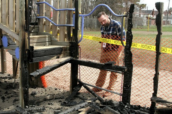 Hyde Park Public School principal Darren Lentz surveys the damage from an overnight fire that burned the school's playground equipment.