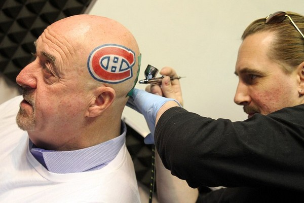 Rob Bates (right) puts the finishing touches on a temporary Montreal Canadiens logo on Mayor Keith Hobbs' head Tuesday morning in the CKPR studios.