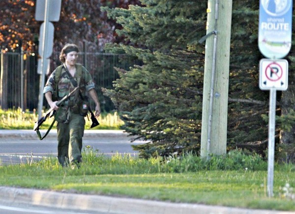 A heavily armed man that police have identified as Justin Bourque walks on Hildegard Drive in Moncton on Wed. June 4, 2014 after several shots were fired in the area.