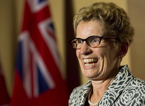 Ontario Premier Kathleen Wynne smiles as she speaks to the media after winning a majority government at Queen