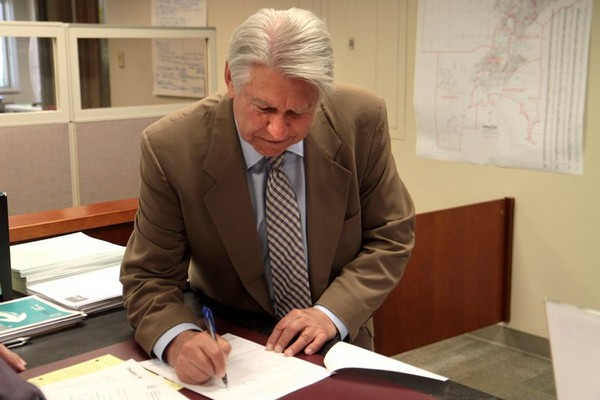 At-large Coun. Ken Boshcoff signs his papers to run for mayor Tuesday morning.