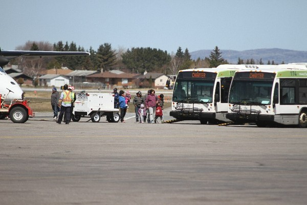 FILE -- Residents of Kashechewan arrive at the Thunder Bay International Airport in May after fleeing from their flooded home community. The nearly 600 residents temporarily living in Thunder Bay are expected to start their return home soon.
