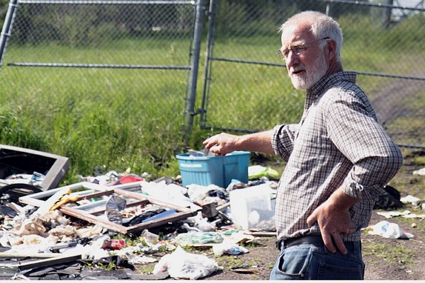 John Woodcock points out one of the primary clusters of garbage that has been dumped on McKellar Island