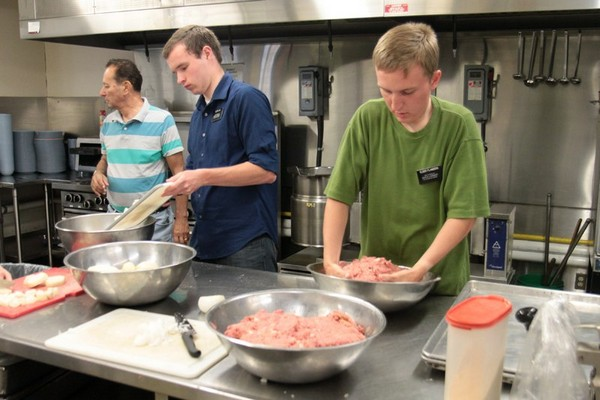 Volunteers help out in the kitchen at Shelter House Thursday morning.