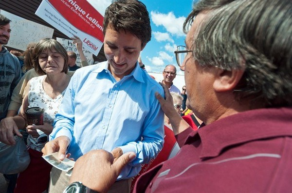 A man shares pictures with Liberal Leader Justin Trudeau during a campaign stop with New Brunswick Liberal Leader Brian Gallant in Moncton, N.B. on Saturday, August 23, 2014.