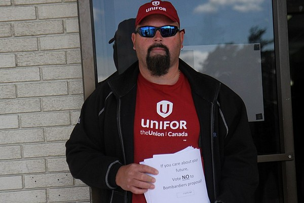 A Unifor Local 1075 member stands outside the Airlane Hotel on Tuesday while fellow striking workers cast ballots in a Ministry of Labour vote on Bombardier